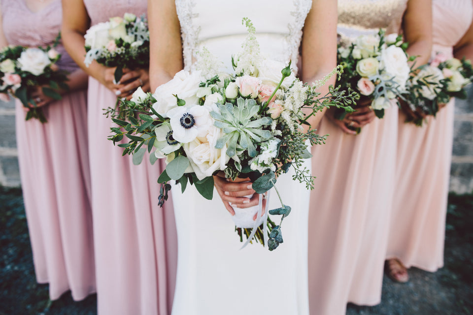 Photo of a bride in a white dress and bridesmaids in pale rose gold dresses, holding anemone, succulent and garden rose bouquets