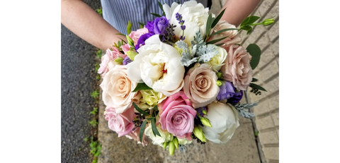 florist holding a white blush and lavender bouquet with quicksand roses and peony