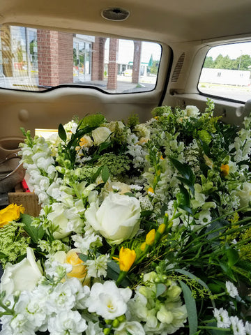 station wagon full of white and yellow floral arrangements