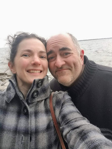 middle aged couple taking a selfie in front of the lake