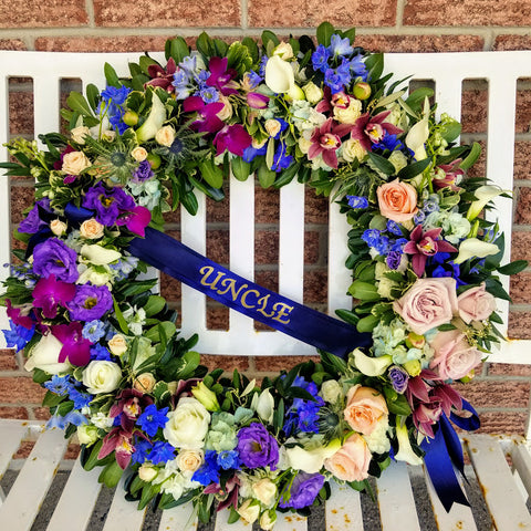 funeral wreath in blue and purple orchids with a ribbon that says uncle