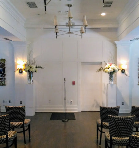 white rental pedestals by sage flowers set up at the Queens University Club in Kingston