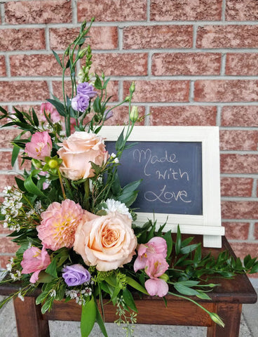 peach and pink flowers framing a photograph or chalk board Kingston ONtario funerals