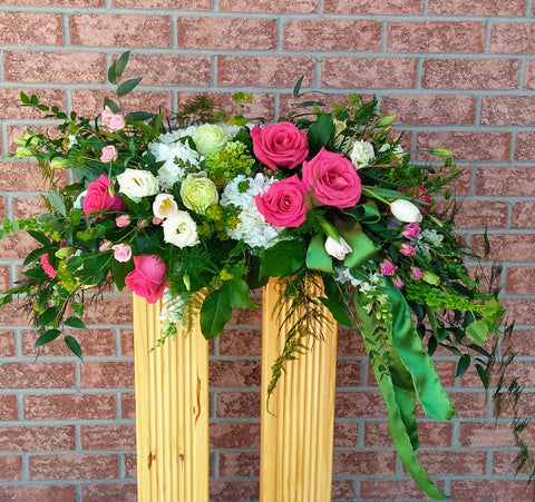 casket spray in white, green and bright pink. hydrangea, roses and a satin green ribbon