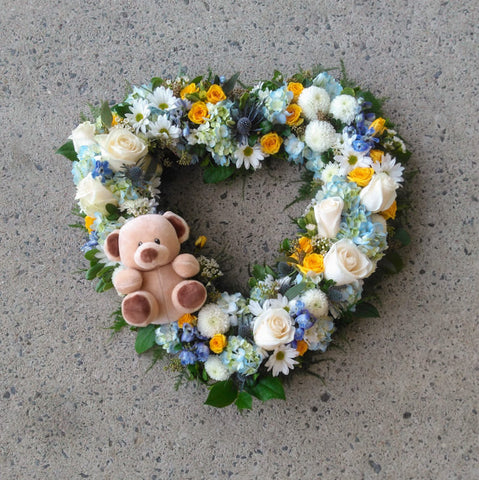 funeral wreath for a child with teddy bear and soft colours