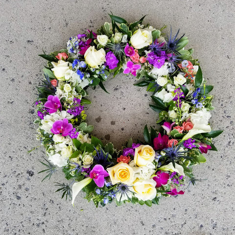 funeral wreath with roses and orchids in blue and purple