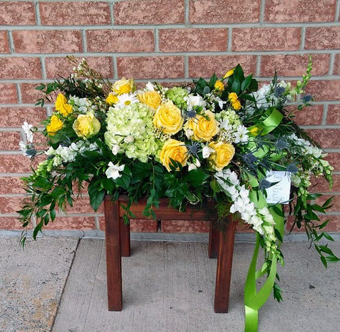 casket spray with yellow white and green blooms and a green satin ribbon