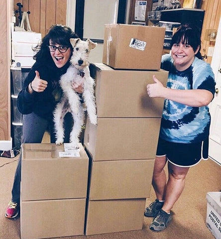 Lauren Beacham and Brittany Elbourn of Yugen Tribe with wire fox terrier dog on pile of package