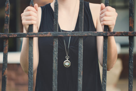 White woman behind bars with celestial pocket watch necklace