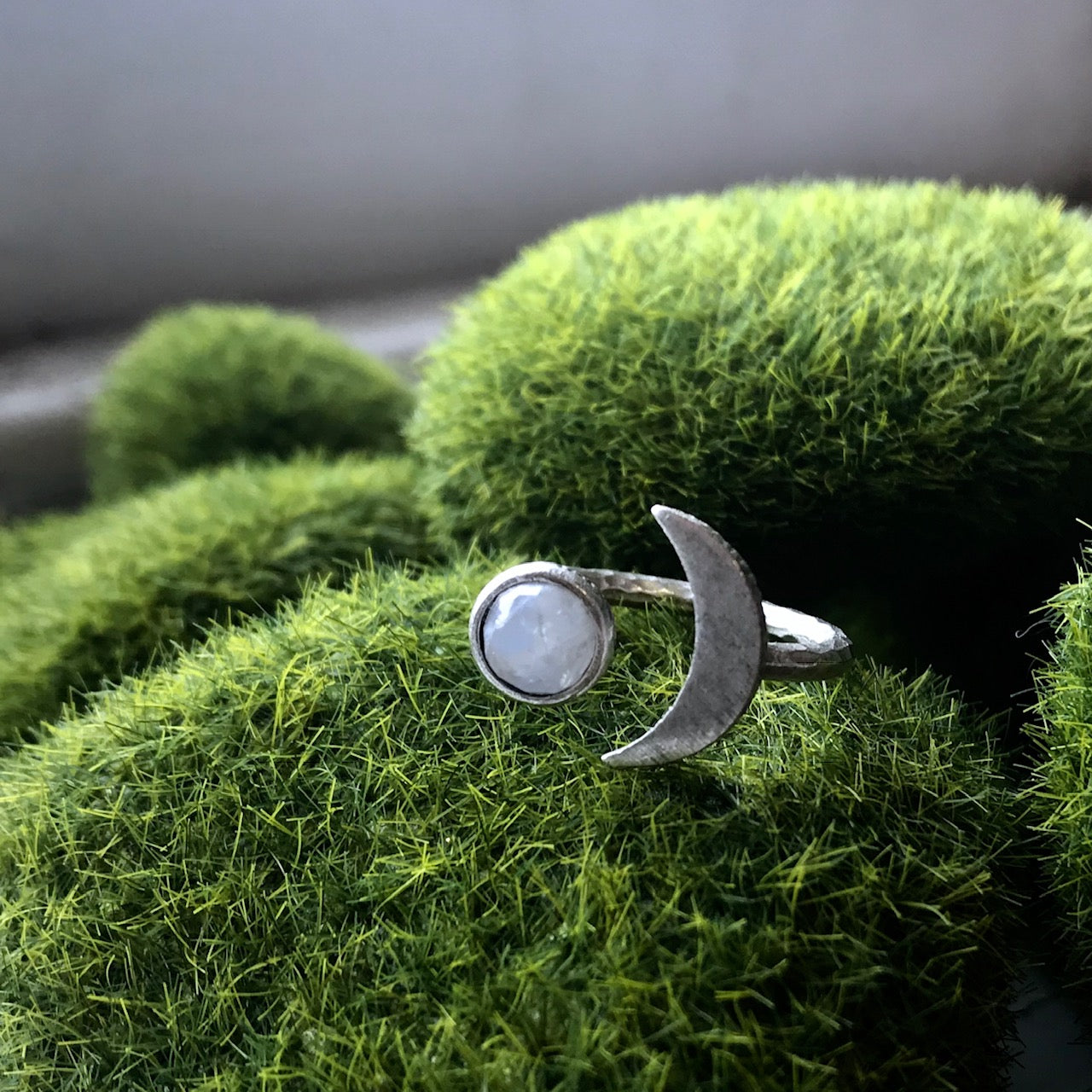 Silver crescent moon ring with rainbow moonstone - handmade jewelry by yugentribe - on green moss rock