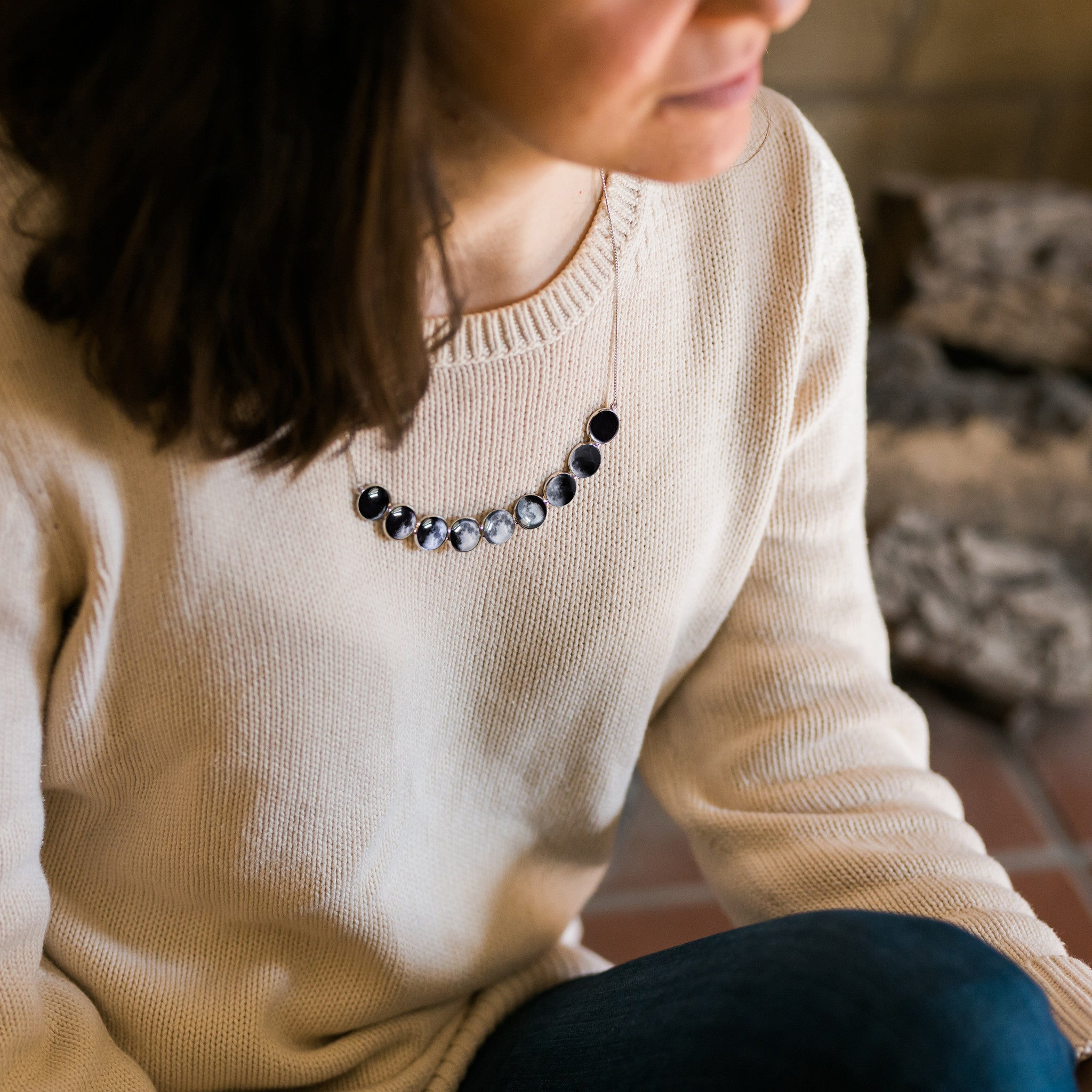 Curved moon phase necklace with 9 different lunar phases - Outer space new age luna jewellery - STEM fashion by Yugen Tribe - modeled by a woman in white sweater