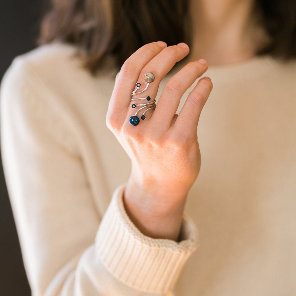 Large cocktail statement ring in silver with black spinel, azurite malachite, and copper calcite - Inspired by the cosmos and the earth, moon, and outer space - Handmade galaxy jewelry by YugenTribe - modeled by white woman in beige sweater