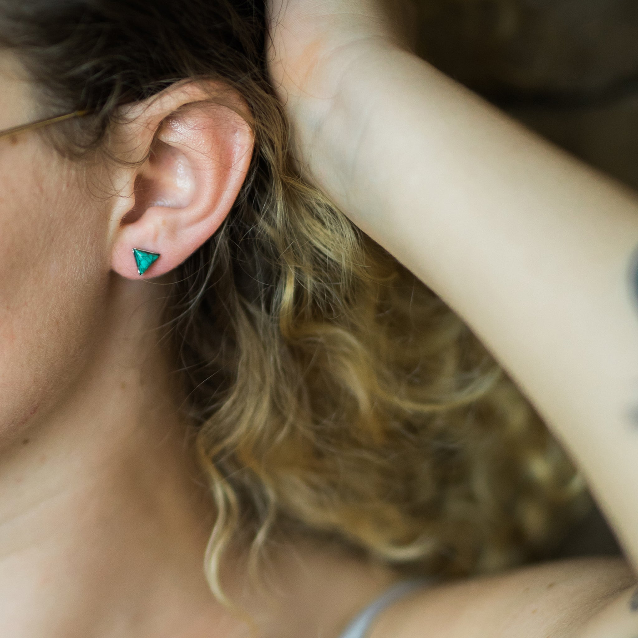 Small tiny petite triangle stud earrings with natural turquoise - December birthstone, minimalist boho jewelry by Yugen Tribe - handmade in USA by women - modeled by blonde white woman with curly hair