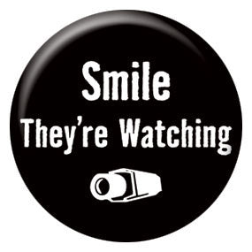 "Smile They're Watching 1"" Button by Seltzer Goods"