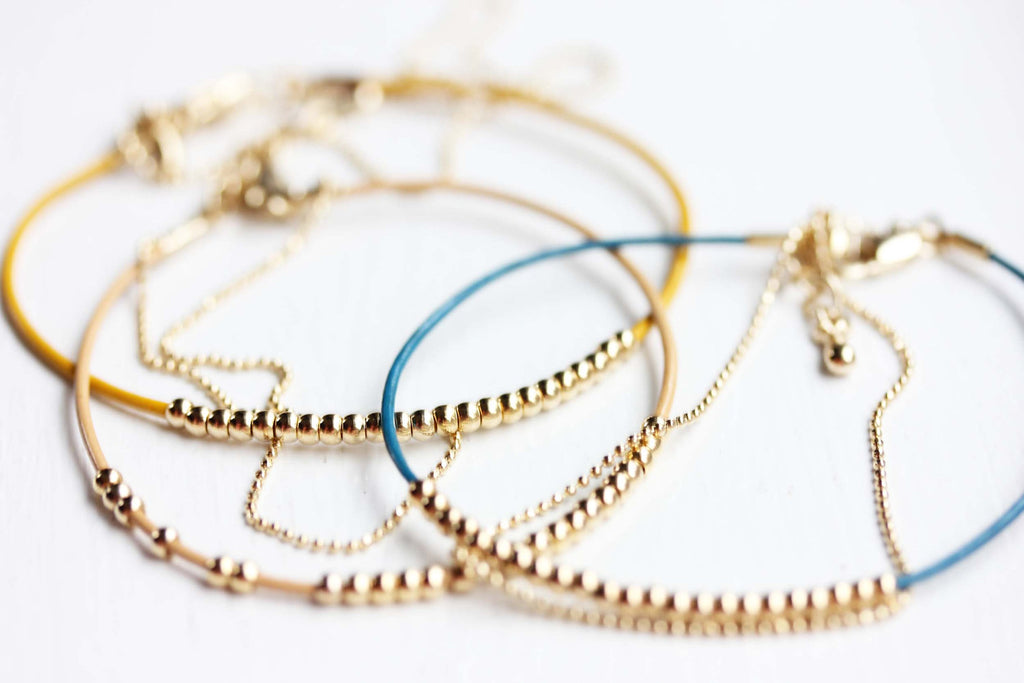 Dainty beaded blue, tan, yellow, and gold bracelets from Diament Jewelry, a gift shop in Washington, DC.