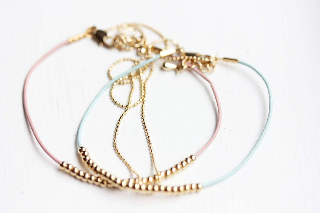 Dainty beaded blue, pink, and gold bracelets from Diament Jewelry, a gift shop in Washington, DC.