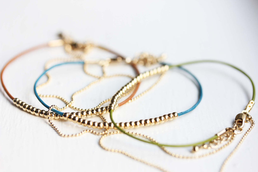 Dainty beaded brown, green, blue, and gold bracelets from Diament Jewelry, a gift shop in Washington, DC.