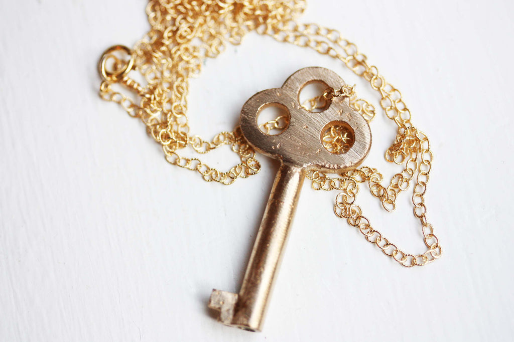 Brushed gold key necklace from Diament Jewelry, a gift shop in Washington, DC.