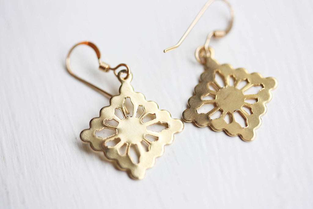 Gold dolly dangle earrings from Diament Jewelry, a gift shop in Washington, DC.