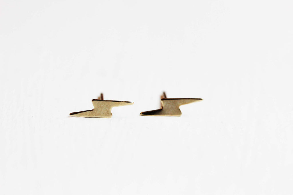 Tiny gold lightning bolt studs from Diament Jewelry, a gift shop in Washington, DC.