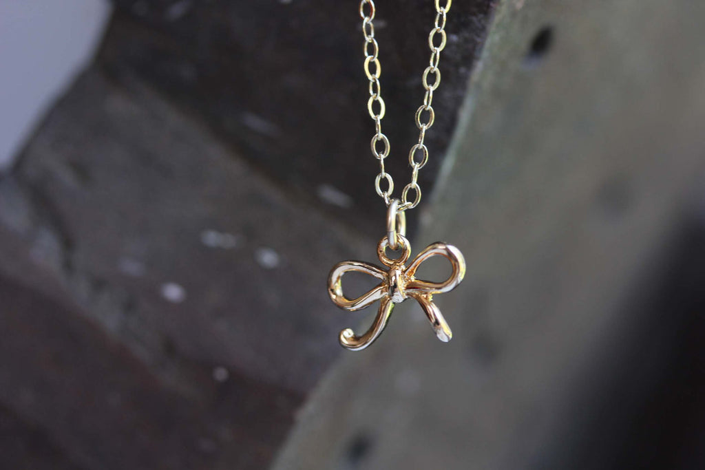 Tiny gold bow necklace from Diament Jewelry, a gift shop in Washington, DC.