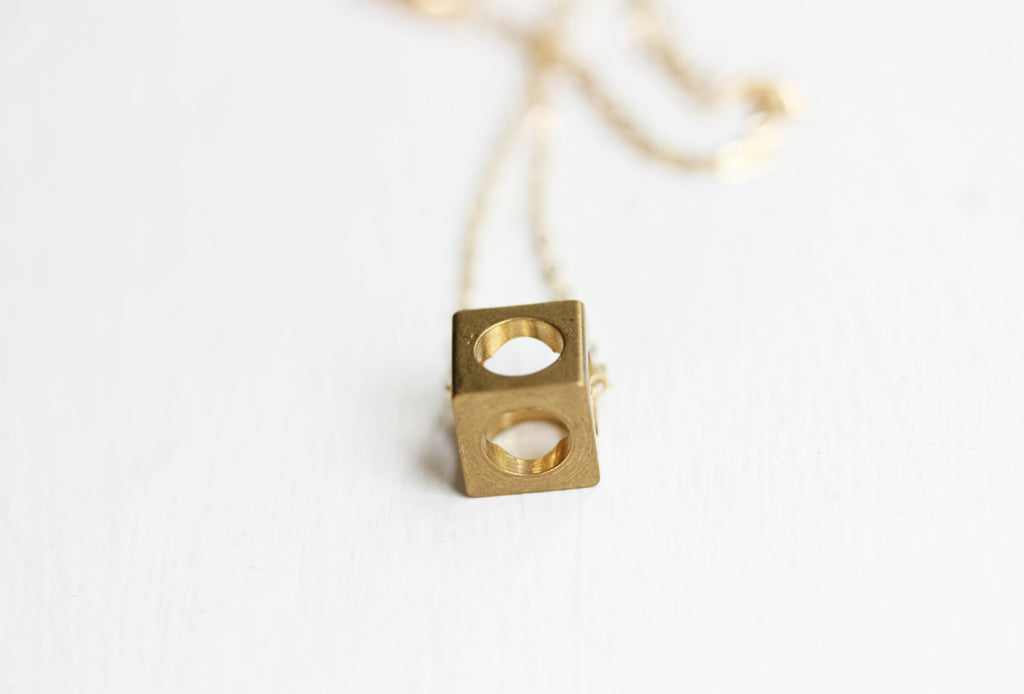 Tiny Brass Cube Necklace from Diament Jewelry, a gift shop in Washington, DC.