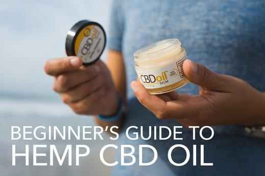 a white person in a blue t shirt holding a jar of CBD salve opened with the words beginners guide to hemp cbd oil in white