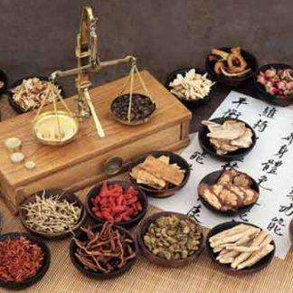 brass scale on a wooden box surrounded by black bowls containing different herbs, and a white paper with Chinese characters on it