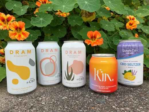 Cans of dram, kin, and queen city hemp beverages in a row inn front of flowers