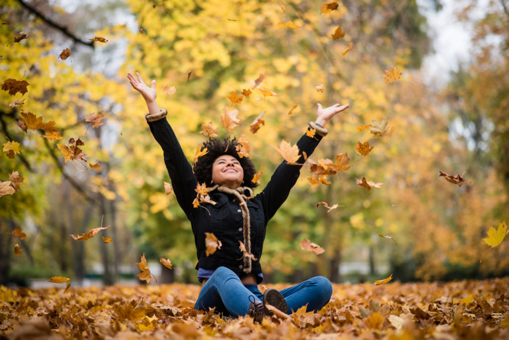 Young black woman sitting in fall leaves throwing them up into the air with yellow fall trees behind her