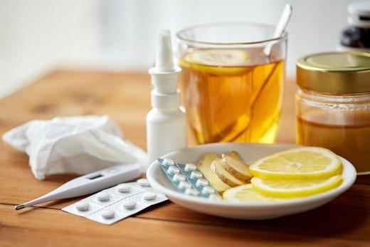 wooden table top with a clear glass of tea, a thermometer, a nose spray, and a plate of lemon slices and blister pack of pills