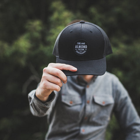 Black Almond Trucker Hat
