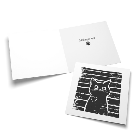 Card with a whimsical hand carved lino print cat wearing a heart on it's chest. The inside of the card says, thinking of you.