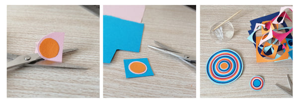 Scissors cutting the pink paper around the orange circle that is glued on the pink.
