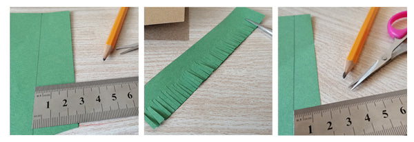 Green paper, a ruler, and a pencil. Scissors cutting slits into the green paper to make grass.