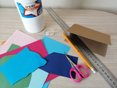A bottle of glue, colourful paper, scissors, a ruler, a pencil and a brown, folded kraft card.