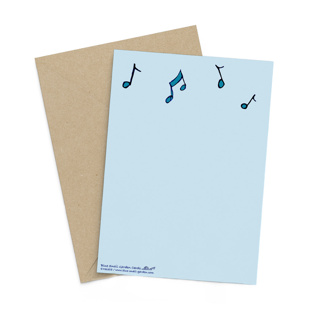 Back of a portrait style, light blue greeting card with turquoise music notes. Envelop in background. Copyright Heidi Etsell