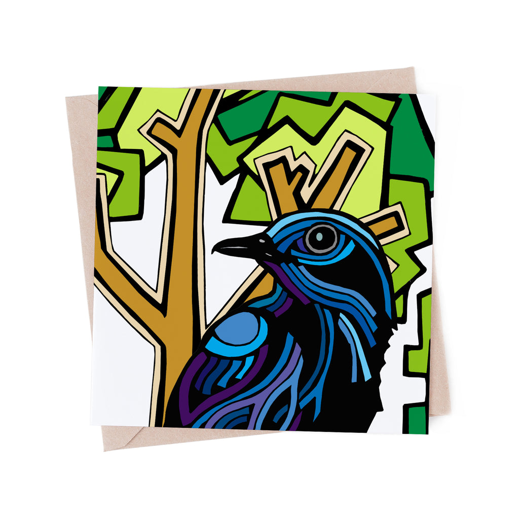 Square greeting card with a stylized, blue bird with a green tree. There is a brown envelope in the background.