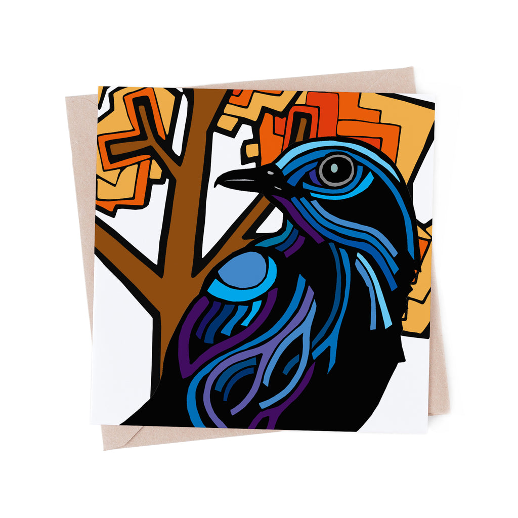 Square greeting card with a stylized, blue bird with an orange tree. There is a brown envelope in the background.