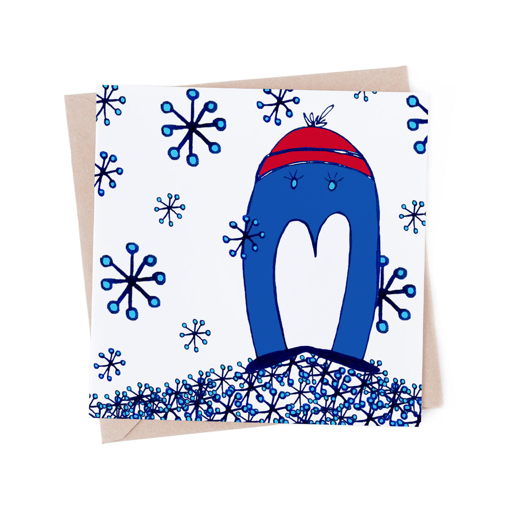 Whimsical blue penguin in a red winter hat, on a greeting card full of snow flakes. A brown envelope is in the background.