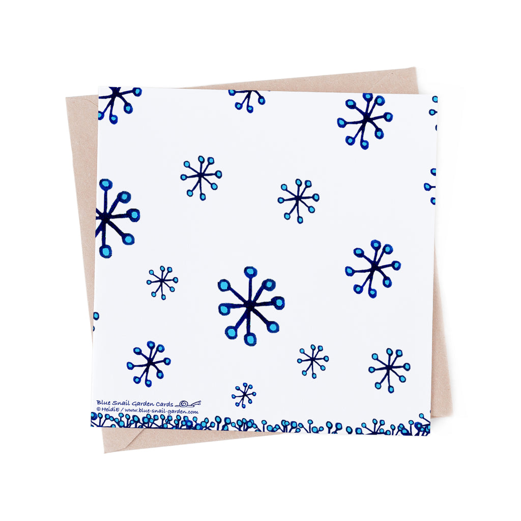 Back of a square, white greeting card with blue snowflakes. Brown envelope in the background. Copyright Heidi Etsell