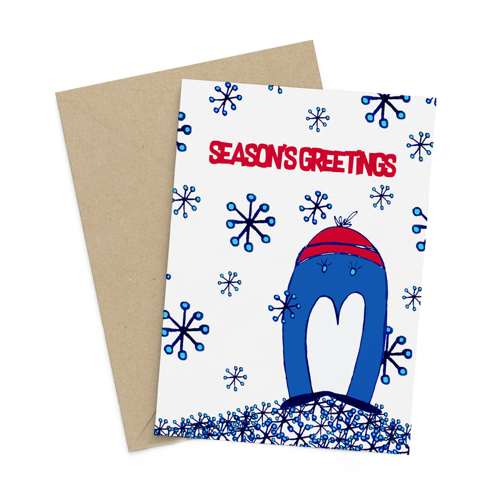 Whimsical blue penguin in a red hat, on a season's greetings card full of snow flakes. A brown envelope is in the background.