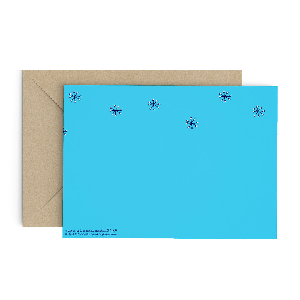 Back of a landscape style, blue greeting card with snowflakes. Brown envelope in the background. Copyright Heidi Etsell