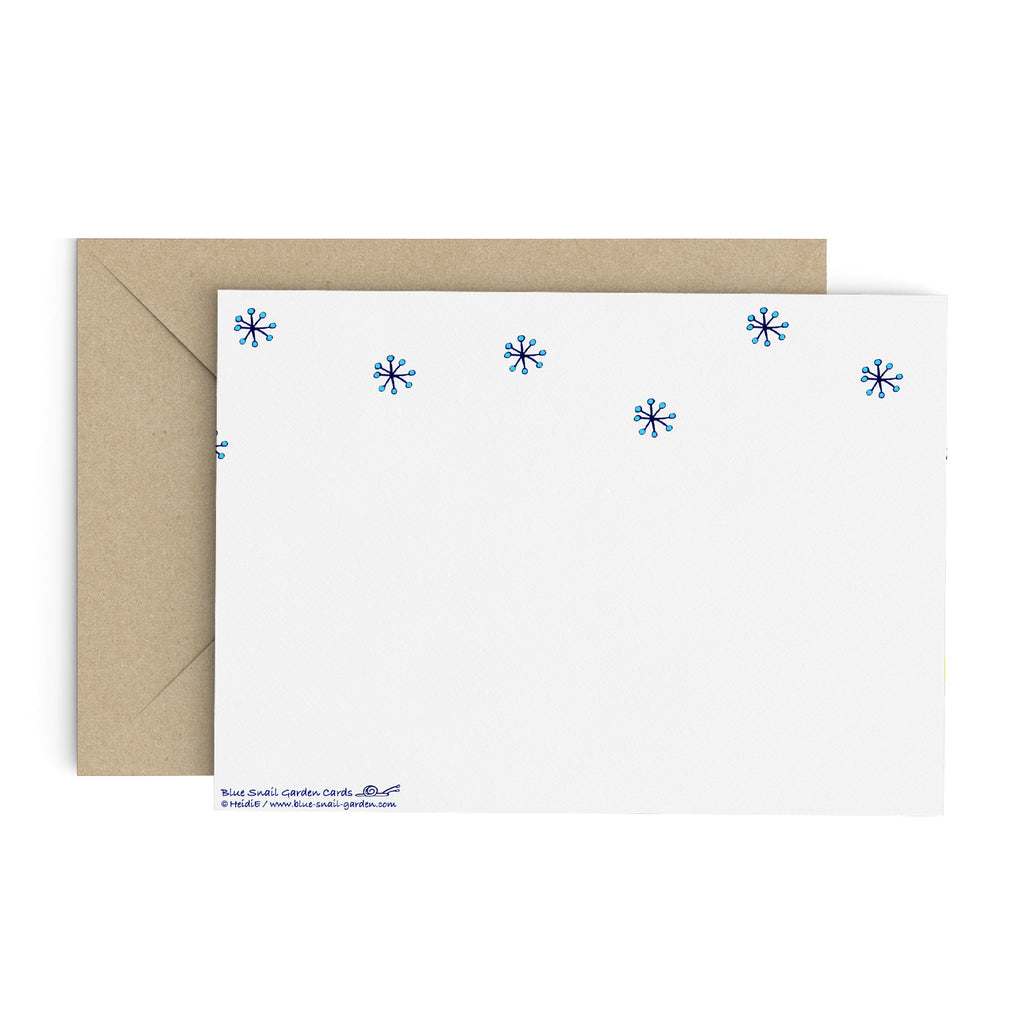 Back of a landscape style, white greeting card with snowflakes. Brown envelope in the background. Copyright Heidi Etsell