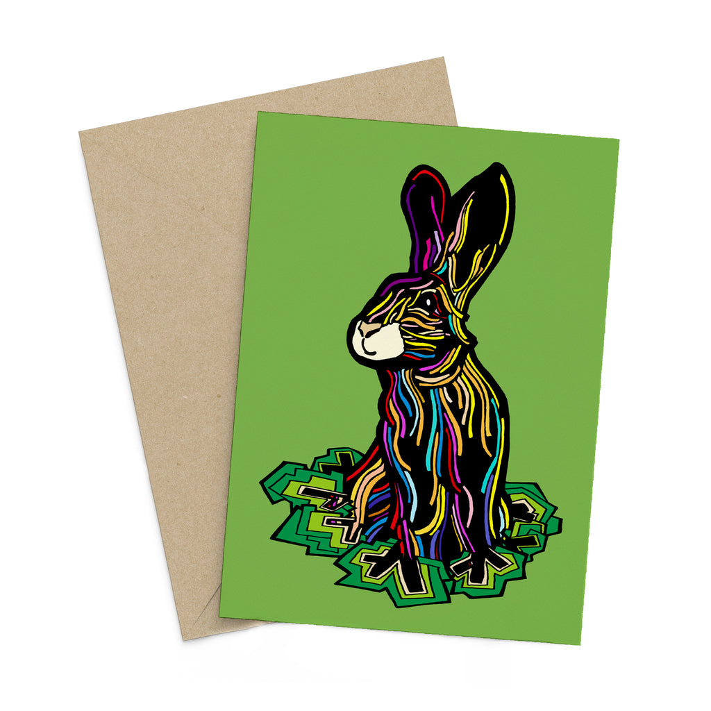 Colourful, stylized rabbit on a green greeting card. A brown envelope is in the background.