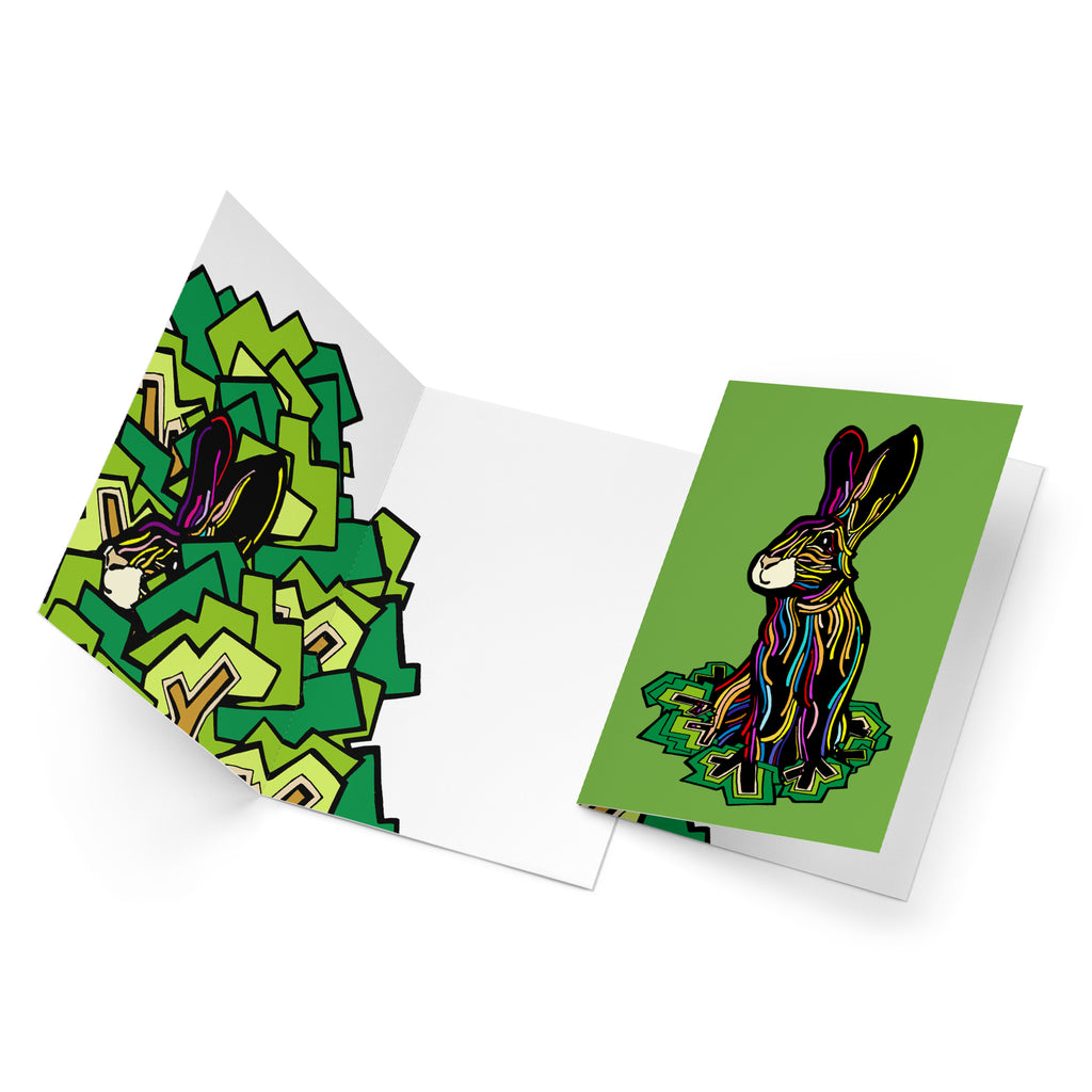 White inside of a portrait style greeting card. A colourful rabbit is peaking out of green bushes on the left side.