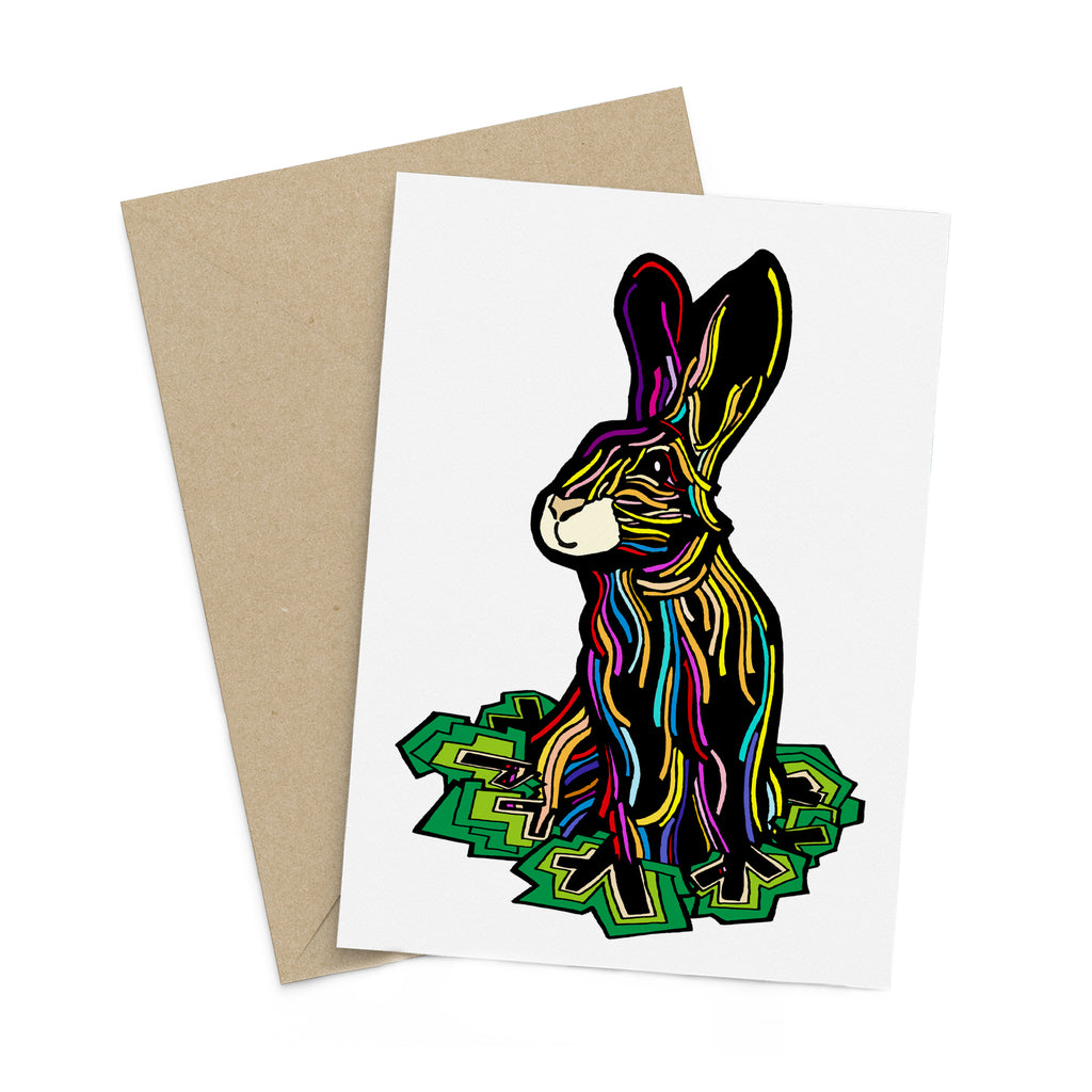 Colourful, stylized rabbit on a white greeting card. A brown envelope is in the background.