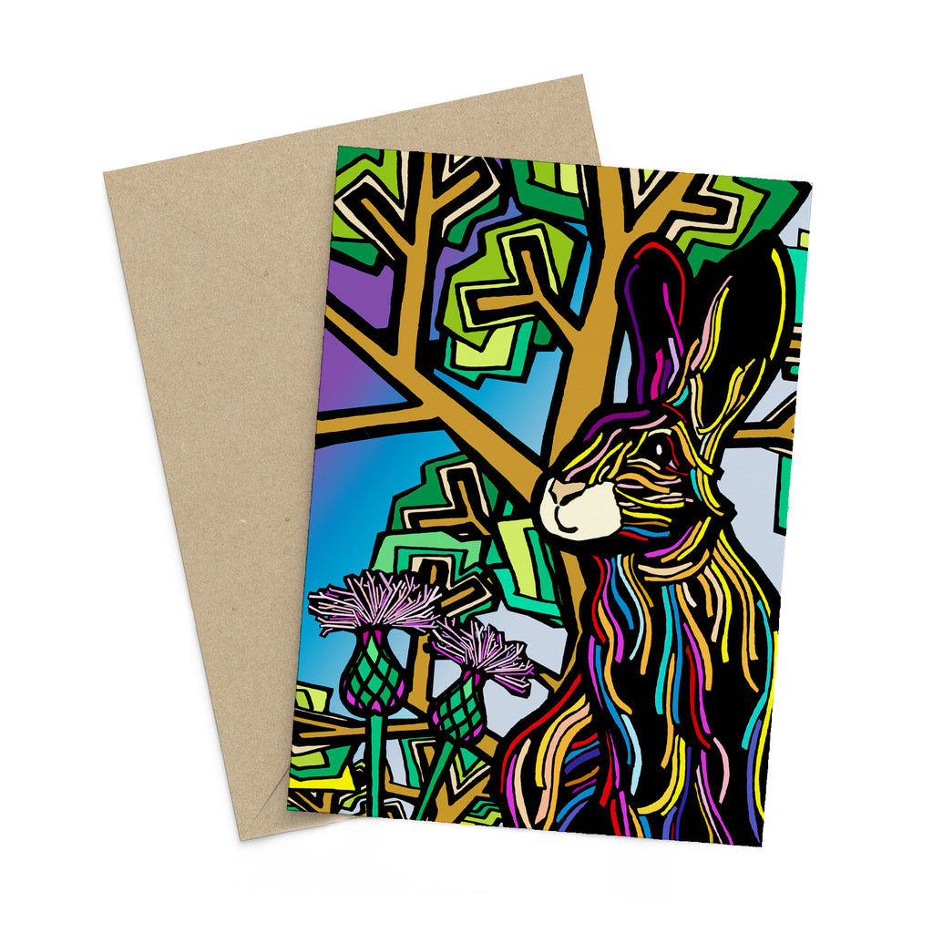 Colourful, stylized rabbit with trees and flowers on a greeting card. A brown envelope is in the background.