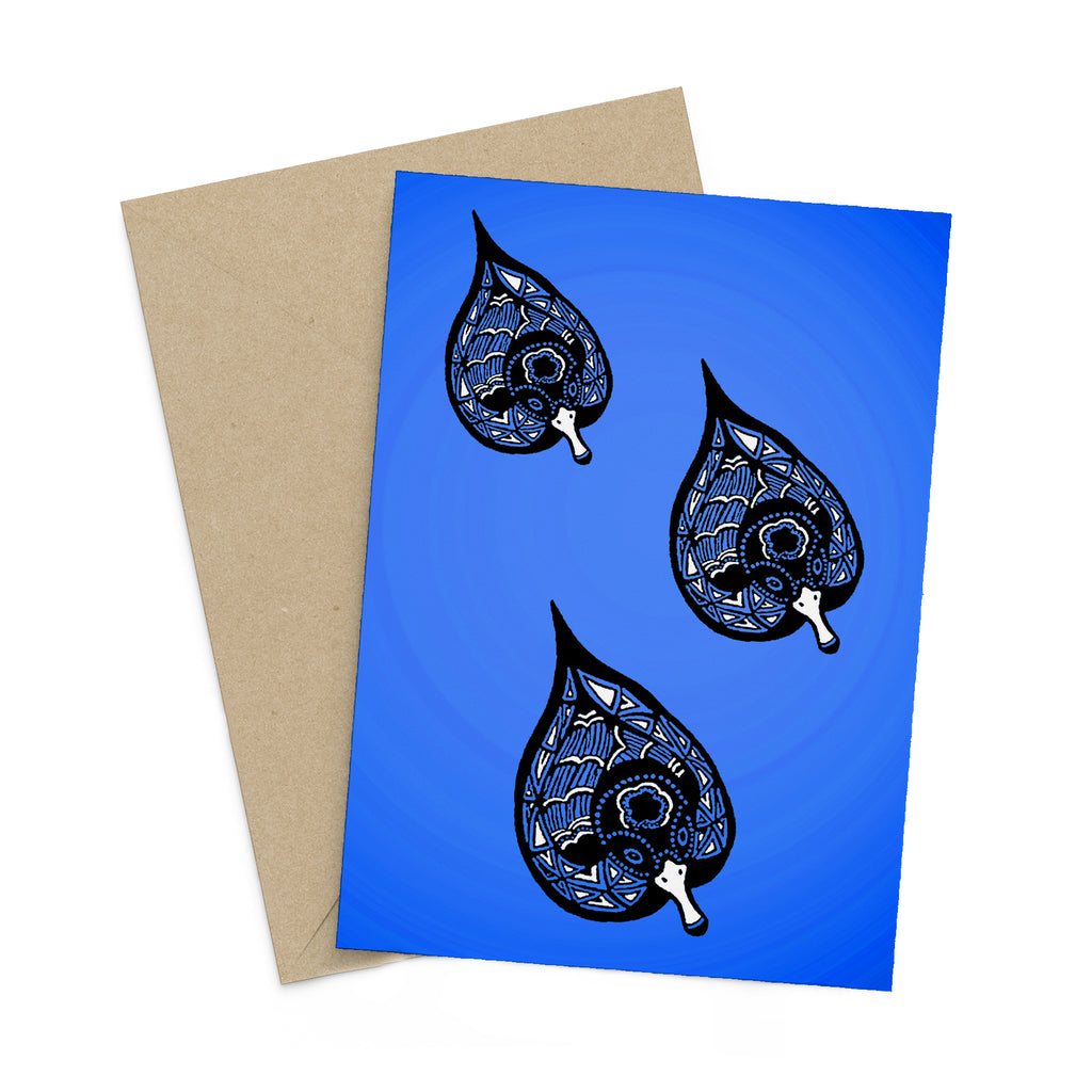 Three stylized, black, white and blue ducklings on a blue greeting card. A brown envelope is in the background.