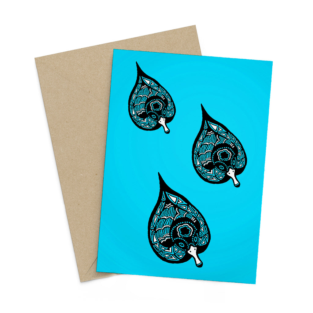 Three stylized, black, white and blue ducklings on a light blue greeting card. A brown envelope is in the background.
